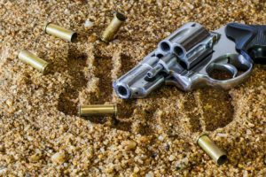 gun and bullets on sand